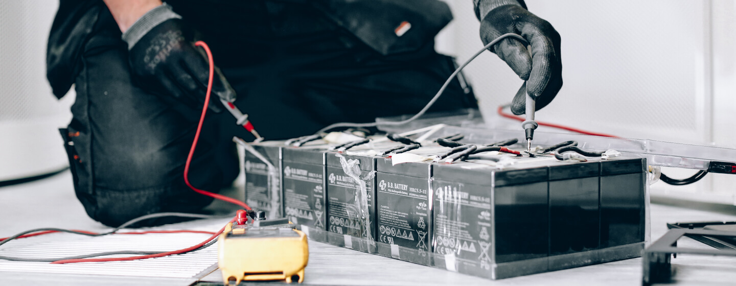 Engineer carrying out impedance testing on a UPS battery